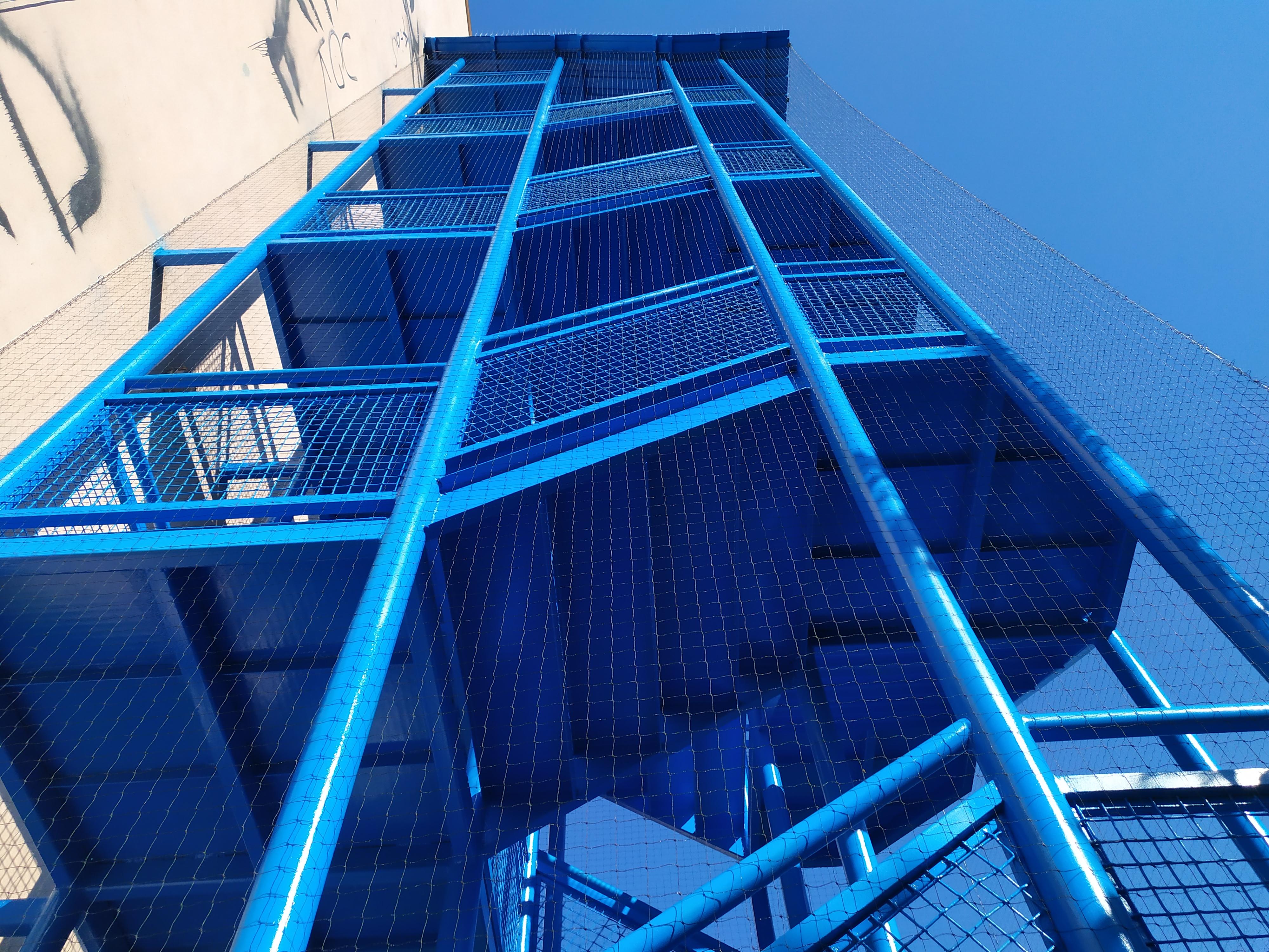 Instalace sítě proti holubům na schodiště v exteriéru budovy v Praze